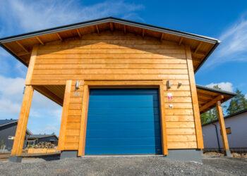 Doorway nosto-ovi DW4 leveä vaakaura tumman harmaa lamelli RAL 7016. Autotallin nosto-ovi hirsirakennuksessa.