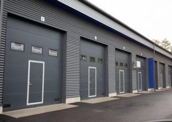 Doorway -nosto-ovi teollisuuteen. Talliosake teollisuuden nosto-ovi käyntiovella ja ikkunoilla.